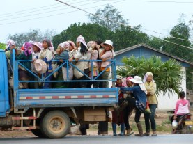Large groups of women board the back of a truck on their way to local market.