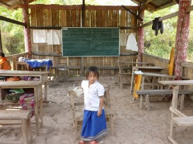 Wary of the foreigner, little girl remains behind in the school room, Somewhere in Laos - Karina Noriega