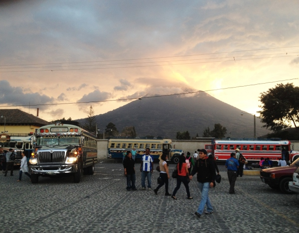 Chicken Bus terminal in Antigua under the looming Volcan de Agua, Guatemala -- April Beresford