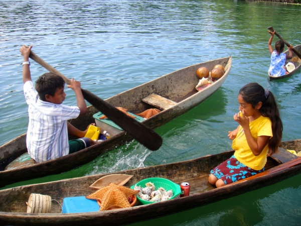 Children selling sea goodies in typical cayucos, Rio Dulce, Guatemala -- Karina Noriega