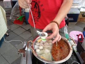 Sampling broth on street in Taipei, Taiwan - Karina Noriega